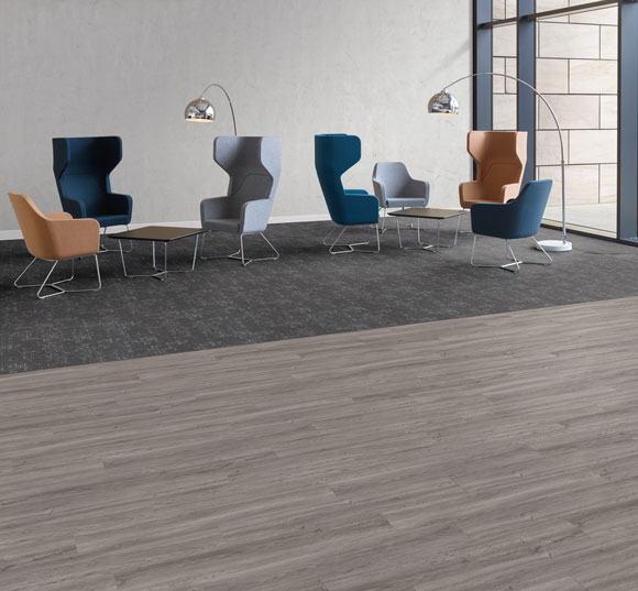An office entrance and breakout space are divided with a change of flooring. Loose Lay Access Cavalier Oak and Sierra Fog carpet tile are used here.